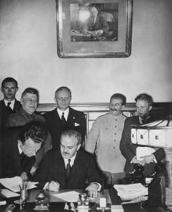 V. M. Molotov podepisuje německo-sovětskou smlouvu o neútočení. Za ním je vidět J. Ribbentrop (v černém) a ve světlém saku J. V. Stalin.