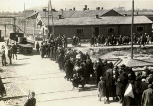 Fronta nic netušících lidí směřujících k plynové komoře a krematoriu